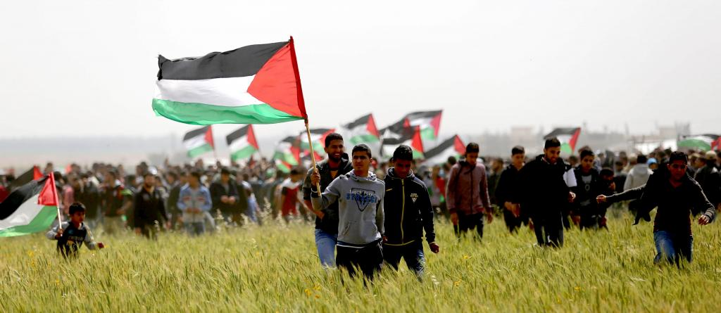 Palestinians take part in the Great March of Return in Gaza, Palestine, on Land Day, 30 March 2018. A crowd is gathered in a green field, holding Palestinian flags. Photo: Ashraf Amra/APA/Shutterstock