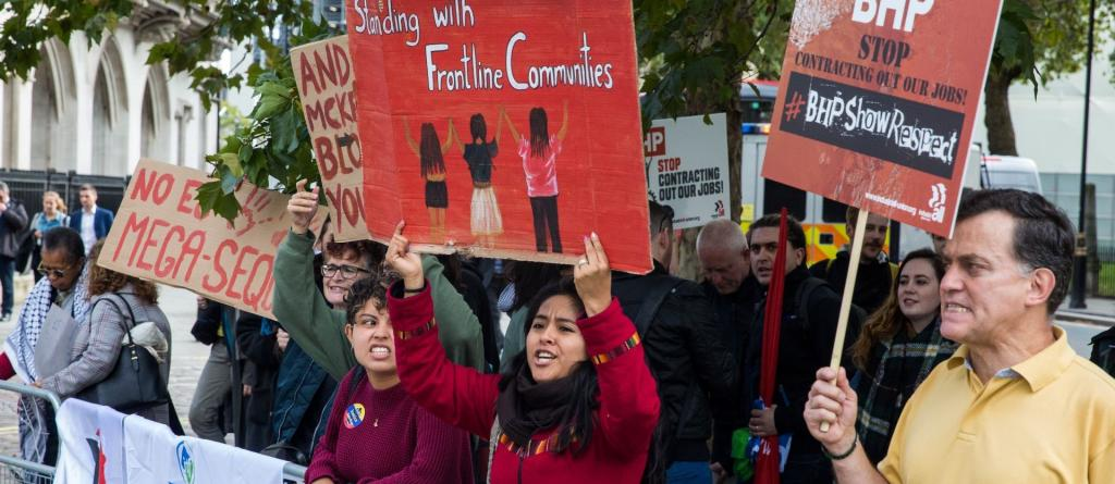 "Protesters at BHP's AGM in 2019 hold placards including ""Standing with frontline communities"" and ""BHP: Stop contracting out our jobs."" Photo: Mark Kerrison."