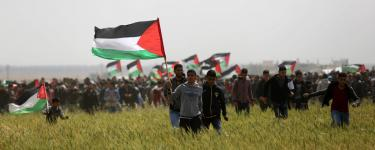 Palestinians with flags at the Great Return March in Gaza. Credit: Ashraf Amra / APA Images
