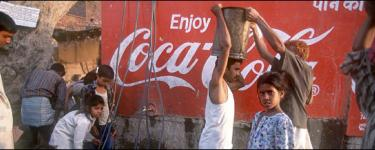People standing in front of a Coca-Cola advert. One person with a white vest an moustache is passing a large drum that he is carrying on his head to another person.