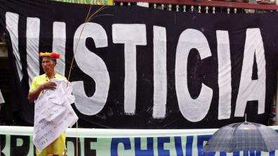 "An indigenous man with stands in front of a giant banner that says ""Justicia"""