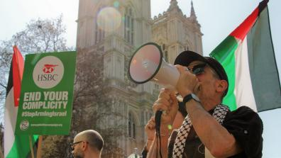 "A protestor speaking into a megaphone in front of the Palestinian flag. A placard to the left reads ""HSBC: End Your Complicity""."