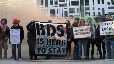 "Campaigners hold placards and banners that read: ""Defend the right to demonstrate against apartheid – Join this movement""; ""BDS is here to stay""; Our money, our choices""; ""Defend Local Democracy"". Credit: London Palestine Action"